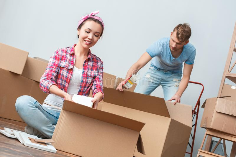 Young couple moving to new place packing things concentrated stock photo