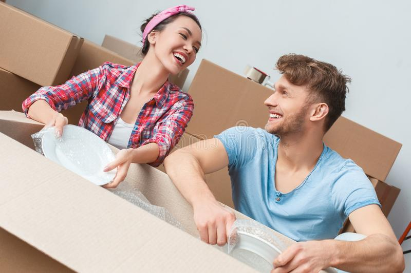 Young couple moving to new place sitting packing things in bubble wrap laughing cheerful stock image