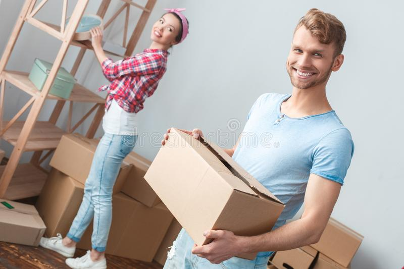 Young couple moving to new place woman standing near shelf while man holding box looking camera cheerful royalty free stock photos