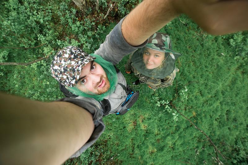 Young couple mushroomers taking photos in forest together. Top view, wide angle. Hiking concept stock images