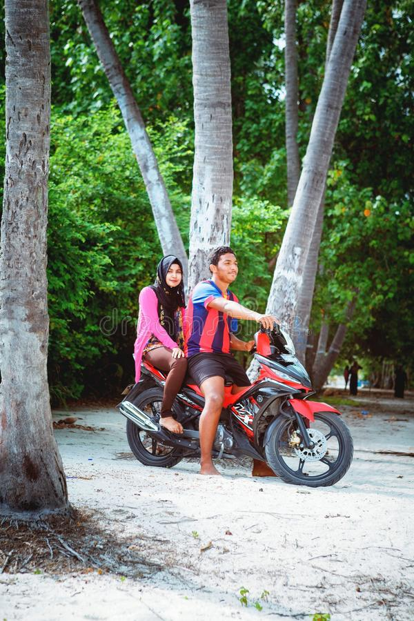 Young couple of muslim sitting on morcicle in the beach of island small village. Fuldhoo, Maldives - December 10, 2016: Young couple of muslim sitting on stock photos
