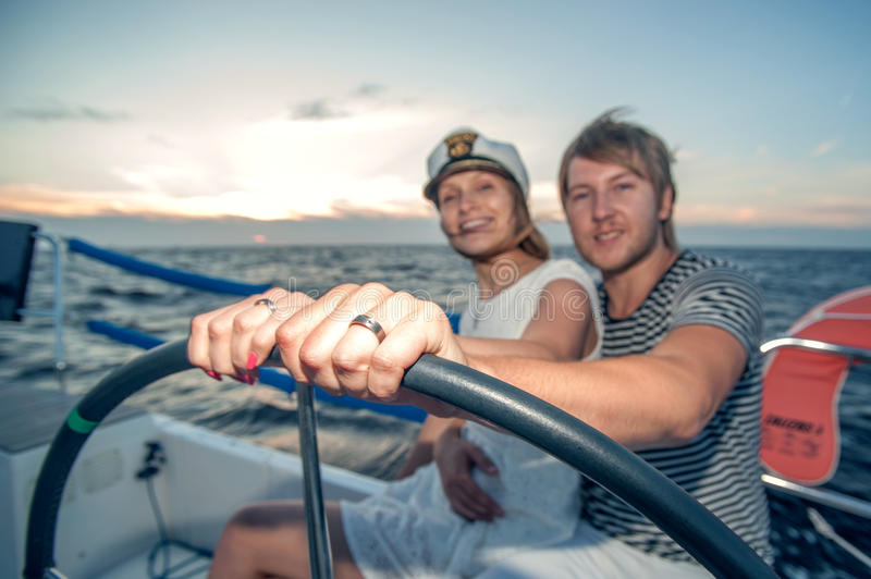 Young Couple Navigating On A Yacht Stock Images