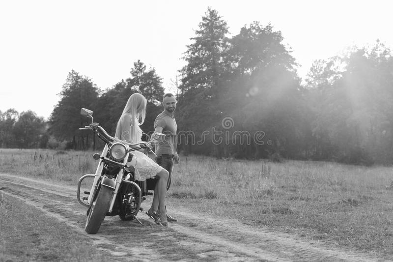 Young couple near the bike in the field. Rest of town. Walking on a motorcycle. Photos for magazines, posters and Web sites royalty free stock photos