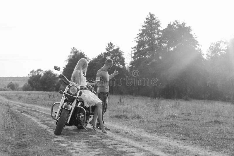 Young couple near the bike in the field. Rest of town. Walking on a motorcycle. Photos for magazines, posters and Web sites stock images