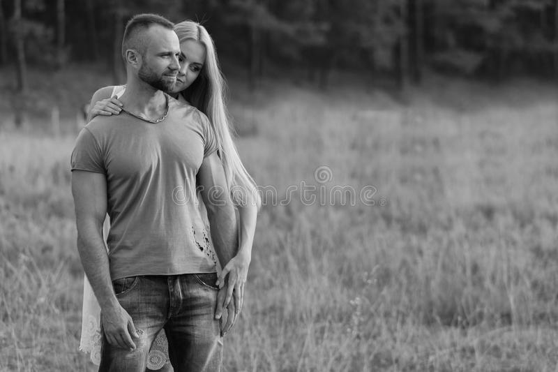 Young couple near the bike in the field. Rest of town. Walking on a motorcycle. Photos for magazines, posters and Web sites stock photo