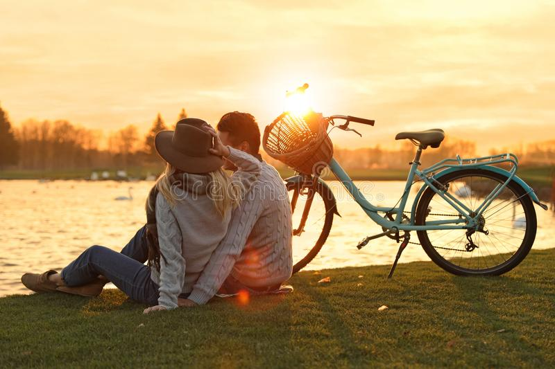 Young couple near lake. Perfect place for picnic. Young couple near lake at sunset. Perfect place for picnic royalty free stock images