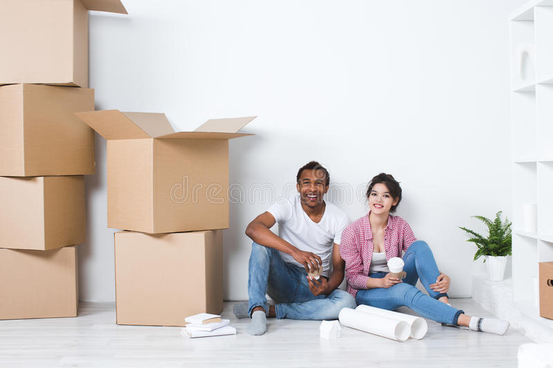 Young couple in a new home relaxing on the background of big boxes. Concept housewarming, began living together stock image