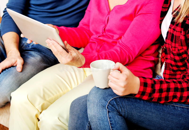 Young couple with old woman sitting on couch and watching something on tablet stock photography