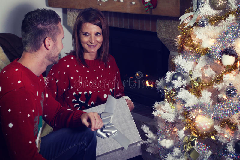 Young couple opening a Christmas present. Next to a fireplace royalty free stock image