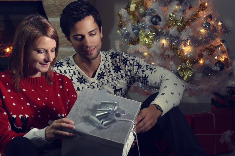 Young couple opening a Christmas present. Next to a fireplace stock photos