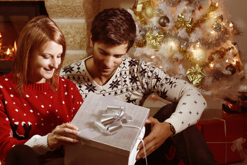 Young couple opening a Christmas present. Next to a fireplace royalty free stock photo
