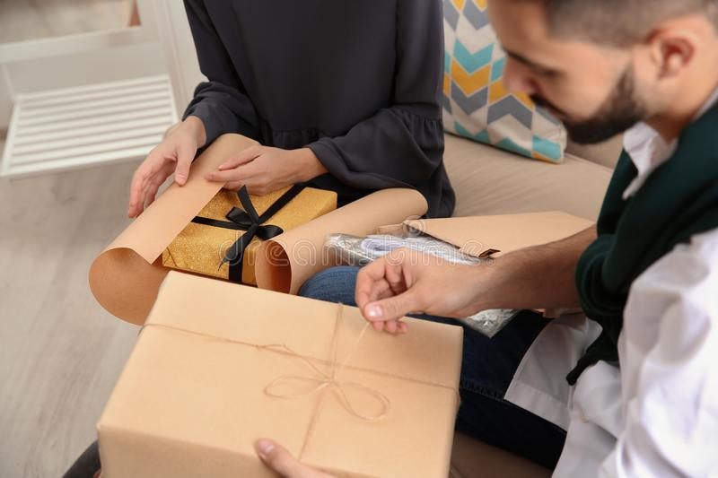 Young couple opening parcels in living room. Closeup stock image