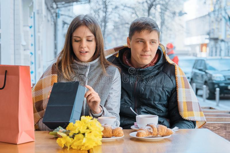 Young couple in outdoor cafe with shopping bags, looking at purchases, drinking coffee after shopping royalty free stock image