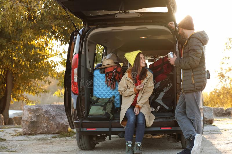 Young couple packing camping equipment into car trunk. Outdoors royalty free stock images