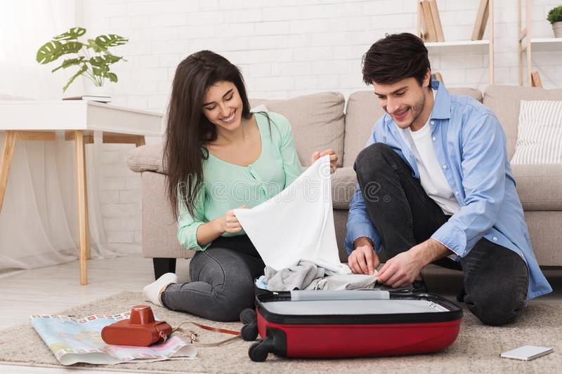 Young couple packing clothes into suitcase at home. Young couple packing clothes into suitcase, preparing for vacation at home royalty free stock photos