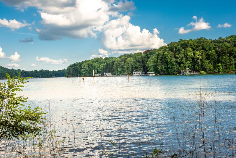 Young couple paddle boarding in Lake Lanier next to waterfront properties stock photos