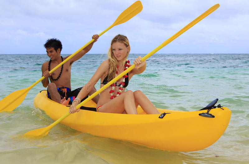 A young couple paddle a kayak in Hawaii