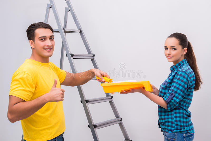 The young couple painting wall at home royalty free stock photography