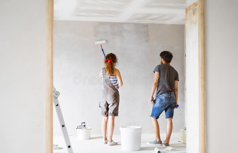 Young couple painting walls in their new house. stock photography