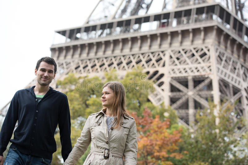 Young couple in Paris. France, in front of Eiffel Tower, walking, holding each other's hands stock photography