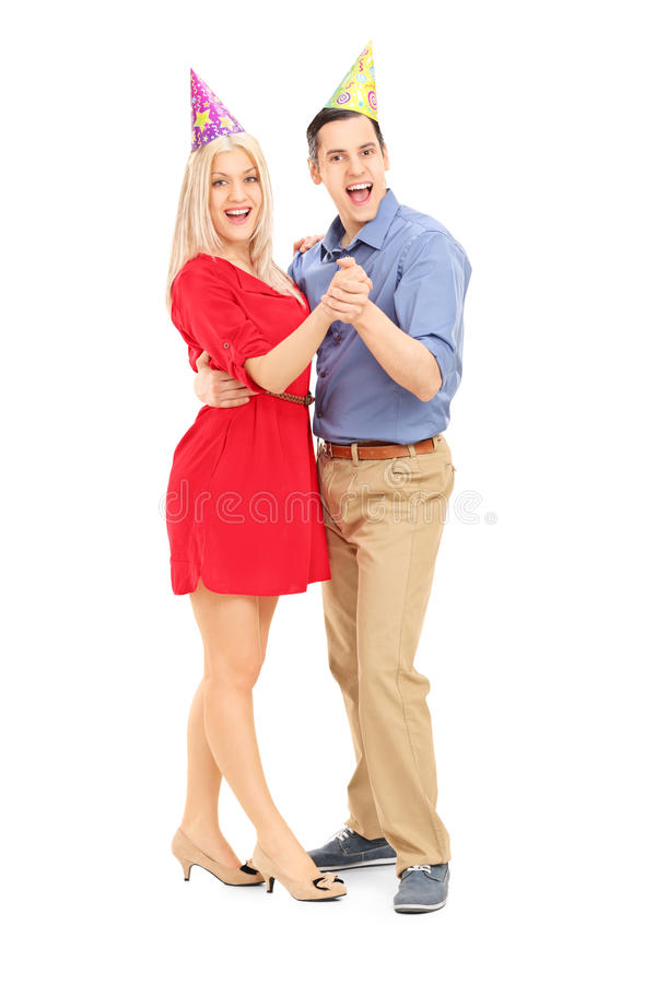 Young couple with party hats dancing stock photos