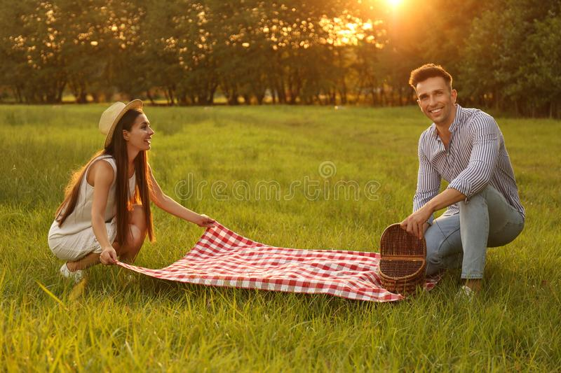 Young couple with picnic blanket and basket stock image