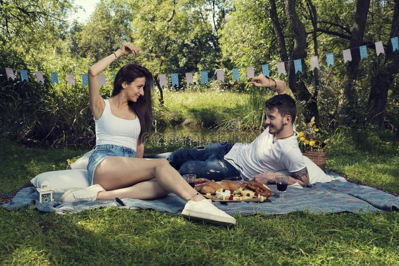 Young couple on a picnic in a city park sitting on a blanket and dueling with skewers with fruits stock photos