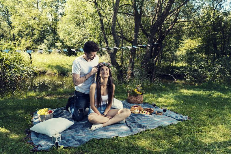 Young couple on a picnic sitting on a blanket The man put on her head flower crown stock images