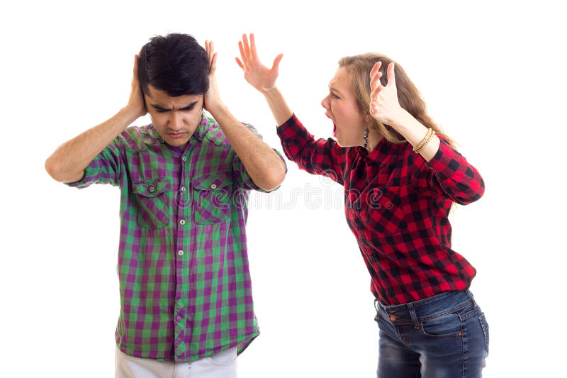 Young couple in plaid shirts arguing. Young angry women with long chestnut hair and young attractive men in plaid shirts arguing on white background in studio stock photo