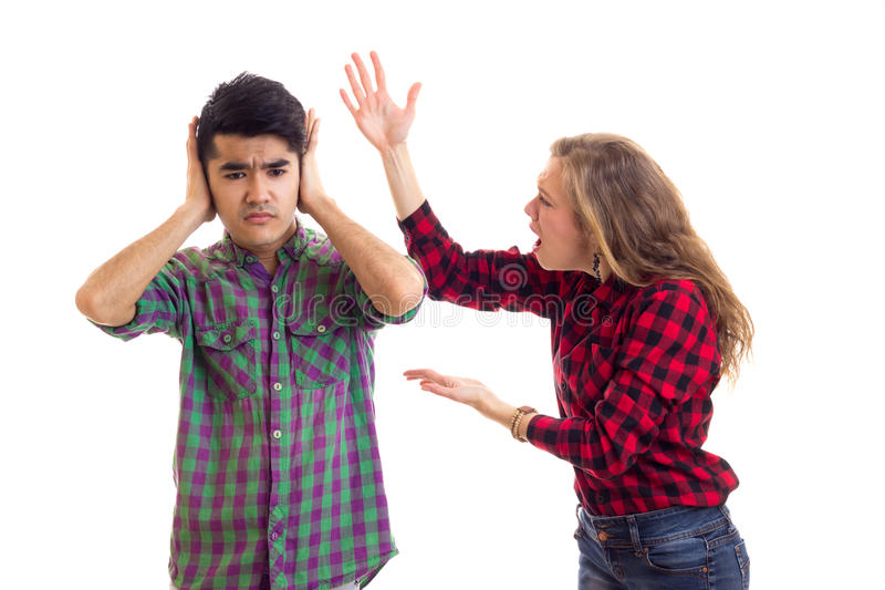 Young couple in plaid shirts arguing. Young angry women with long chestnut hair and young dolorous men in plaid shirts arguing on white background in studio stock photos