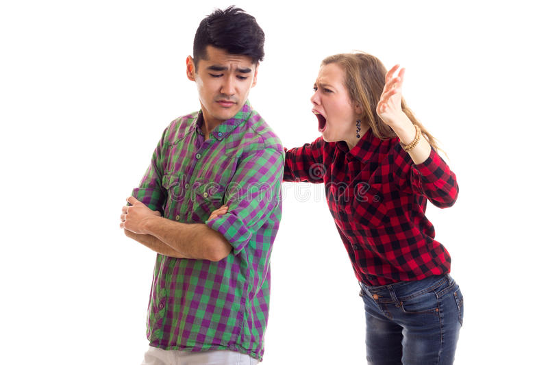 Young couple in plaid shirts arguing. Young angry women with long chestnut hair and young handsome men in plaid shirts arguing on white background in studio royalty free stock image