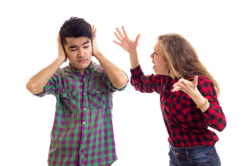 Young couple in plaid shirts arguing. Young angry women with long chestnut hair and young mirthless men in plaid shirts arguing on white background in studio royalty free stock photo