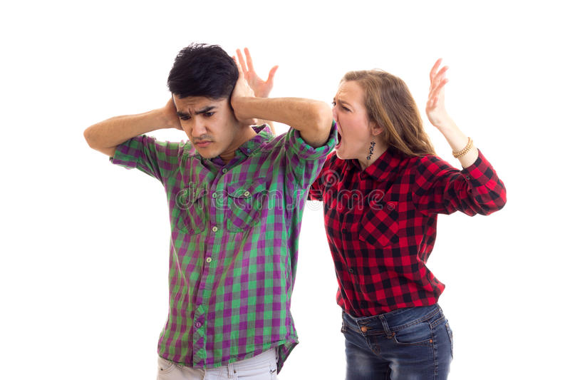 Young couple in plaid shirts arguing. Young angry women with long chestnut hair and young pleasant men in plaid shirts arguing on white background in studio stock images