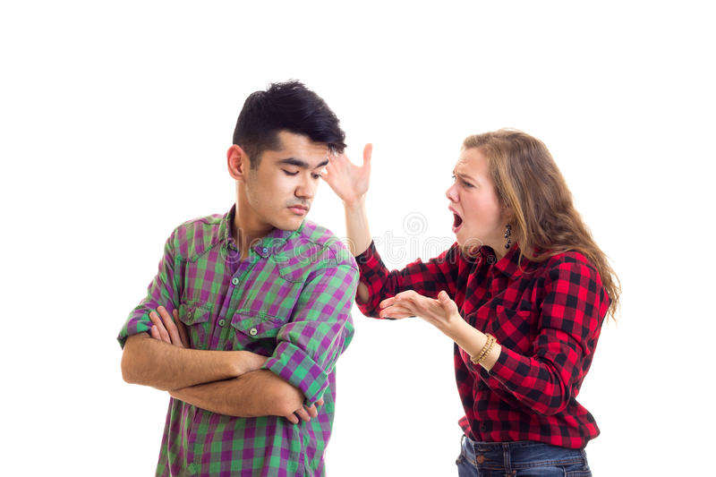 Young couple in plaid shirts arguing. Young angry women with long chestnut hair and young serious men in plaid shirts arguing on white background in studio stock image