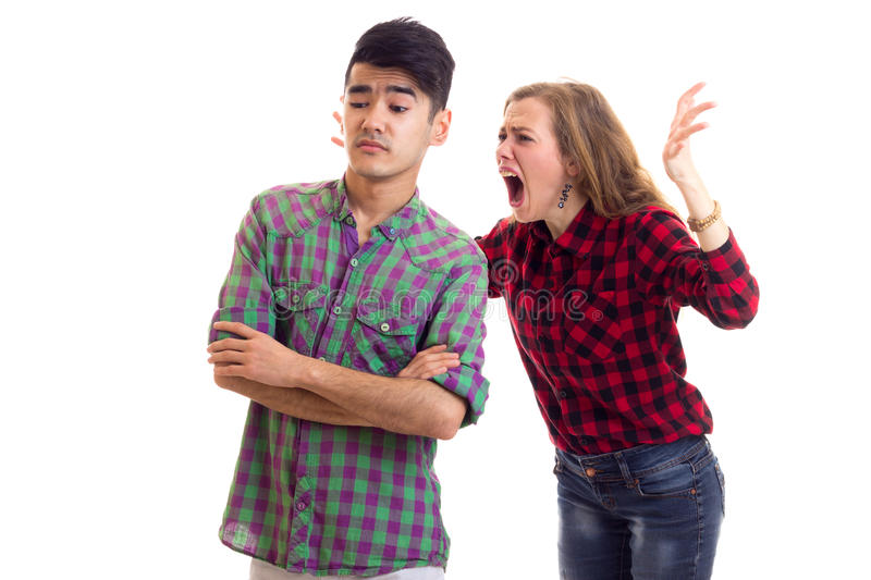 Young couple in plaid shirts arguing. Young angry women with long chestnut hair and young smartlooking men in plaid shirts arguing on white background in studio stock images