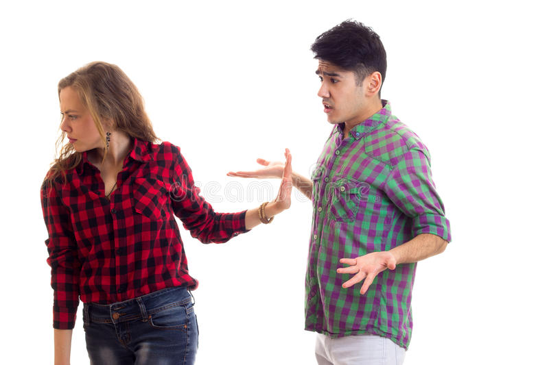 Young couple in plaid shirts arguing. Young dumpish women with long chestnut hair and young handsome men with dark hair in plaid shirts arguing on white royalty free stock photography