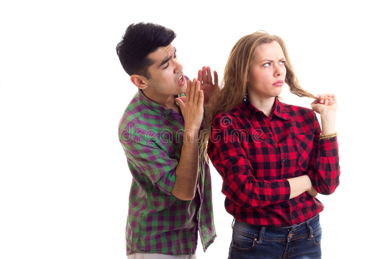 Young couple in plaid shirts arguing. Young sad women with long chestnut hair and young angry men in plaid shirts arguing on white background in studio royalty free stock photos