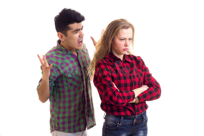 Young couple in plaid shirts arguing. Young sad women with long chestnut hair and young handsome men in plaid shirts arguing on white background in studio stock photography