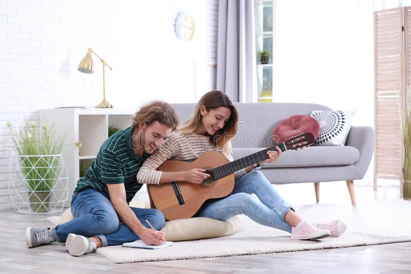 Young couple playing acoustic guitar and composing song in room stock photography