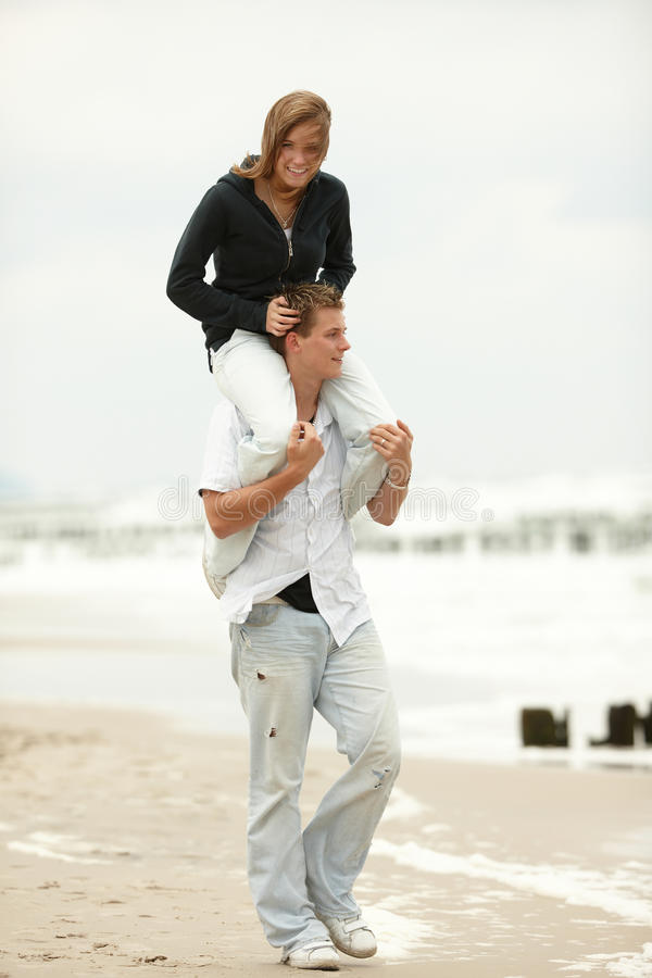 Young couple playing on beach piggyback royalty free stock photography