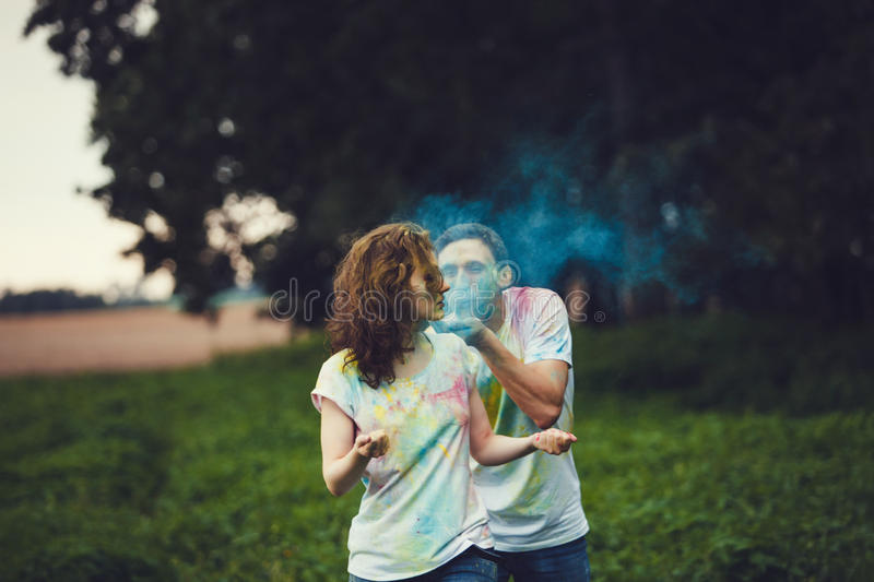 Young couple playing with coloured paint royalty free stock photo