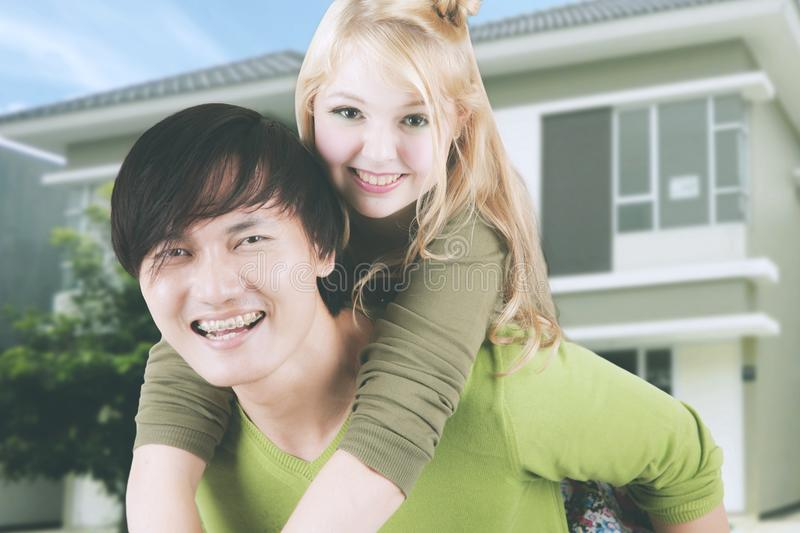 Young couple playing piggyback near their house stock photo