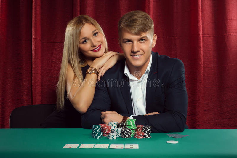 Young couple playing poker at the casino royalty free stock images