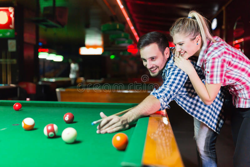 Young couple playing together pool in bar. Young couple playing pool in bar while having night out in town stock photos