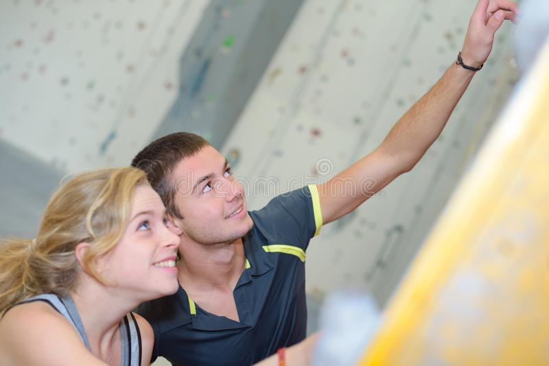 Young couple pointing upwards on climbing wall stock image