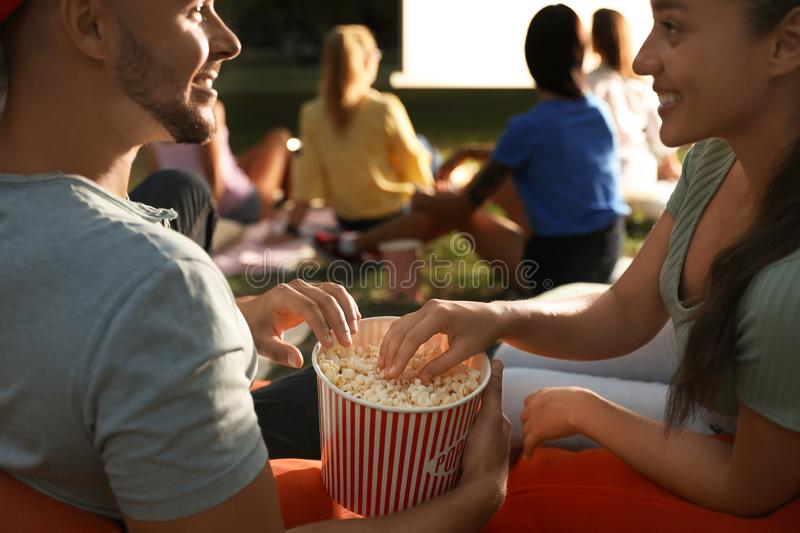 Young couple with popcorn watching movie in open air cinema, closeup stock images