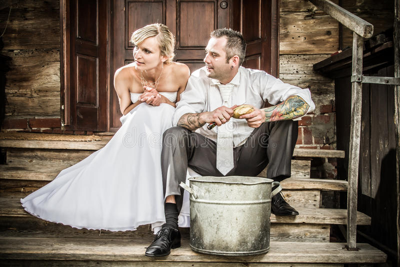 Young couple on the porch peeling potatoes royalty free stock photos
