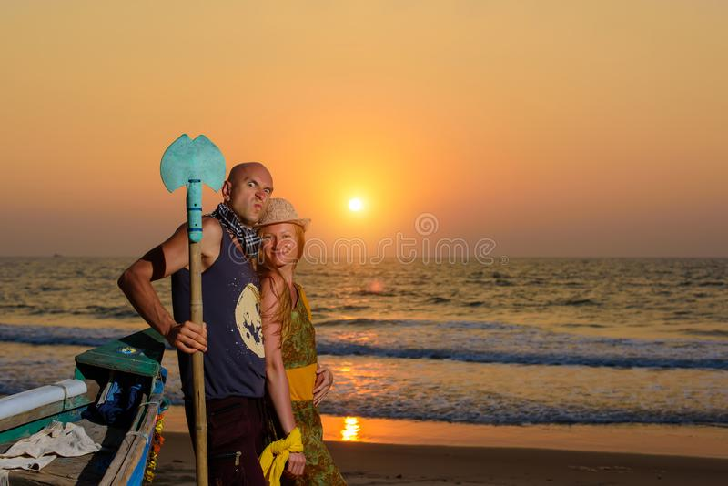 Young couple posing against sea at sunset. Guy and girl fooling and grimace near the old wooden boat on the ocean coast.  stock photo