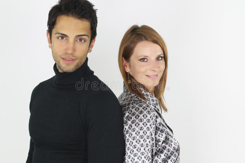 Young couple posing back to back. Over a white background royalty free stock image