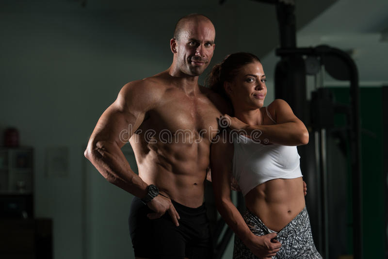 Young Couple Posing In The Gym. Portrait Of A Couple In The Gym With Exercise Equipment stock photography